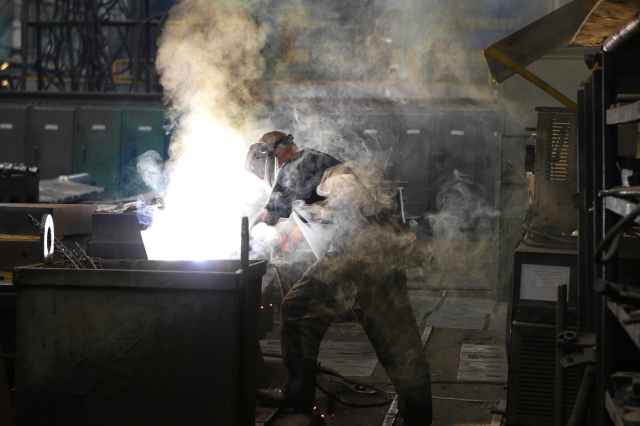 man wearing gray shirt and welding mask covered in welding smokes